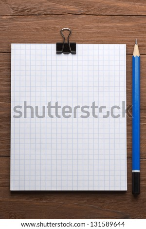 checked notepad and pencil on wood background