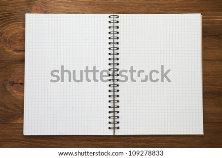 checked notepad  on wood background