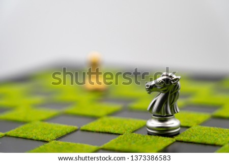 checkerboard background of green grass with knight. Have copy space. one knight can make strong business. Strong leader