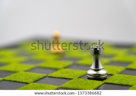 checkerboard background of green grass with rook. Have copy space. one rook can make strong business. Strong leader