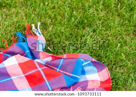 Checkered bright blanket on fresh grass lawn. Vibrant red, green and blue colors. Top view. Copyspace