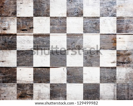 Checkered finish flag painted on grungy wood plank background