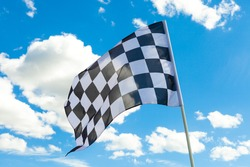 Checkered flag on flagpole waving in the wind with white clouds on background