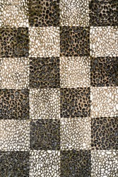 Checkered pattern mosaic floor made of black and white pebbles on the Island of Chios in Greece.