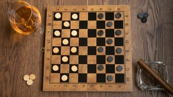 Checkers game board accompanied by a glass of rum and a cigar on a rustic brown wooden table illuminated with natural light
