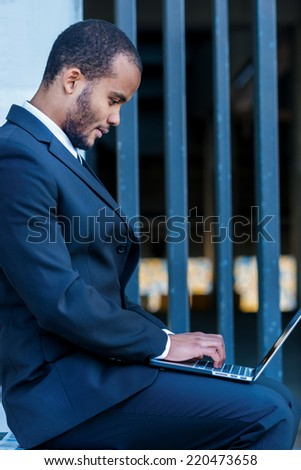 Checking email. Confident man businessman holding a laptop on his knees and looking at the laptop while sitting outdoors in formalwear and prints handed on the keyboard