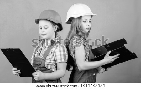 Checking every detail for defects. small girls repairing together in workshop. Foreman inspector. Repair. Labor day. 1 may. teamwork business.. Little kids in helmet with tablet.