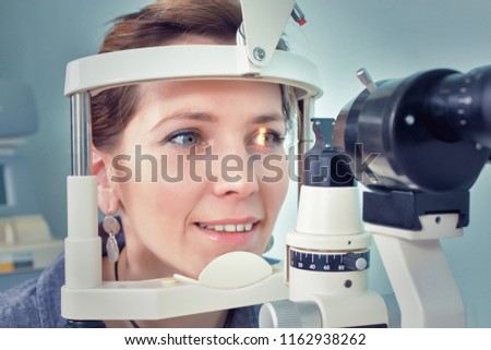 Checking eyesight in a clinic of the future, young girl. Ophthalmology. Future medicine and health concept. Virtual laser for checking vision.
