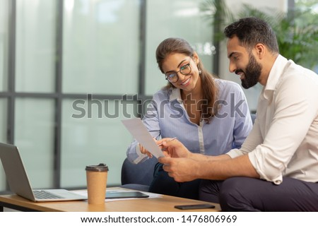 Checking notes. Pleased bearded man sitting in semi position while working at business plan