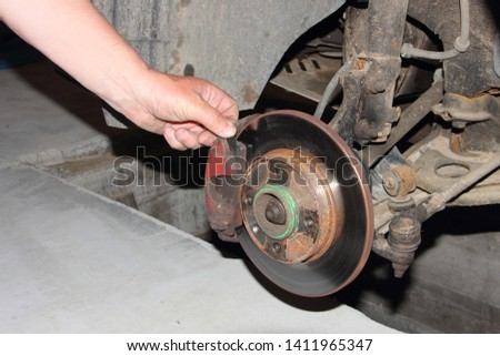 Checking of the brake disc, and brake pads, car brakes inspection - hand points your fingers at the brake caliper #1411965347