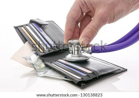Checking open wallet with stethoscope. Concept of financial crisis.
