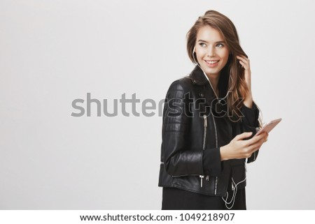 Checking out attractive guy who winking her on street. Good-looking european female standing half-turned, holding smartphone and listening music in earphones, turning back and smiling broadly #1049218907