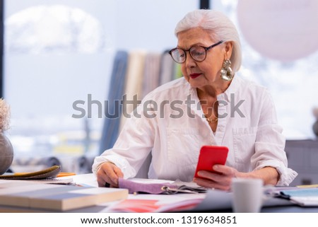 Checking textile quality. Noble elegant elderly grey-haired CEO in fancy white blouse, huge silver earrings and black-rubbed glasses checking textile quality at her office desk
