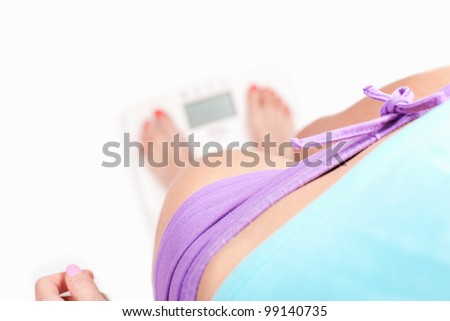 Checking weight, girl standing on digital scale - diet concept, on white background
