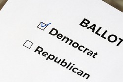 Checklist concept. Closeup of ballot paper with words Democrat and Republican and a pen on it. A checkmark for Democrat in the checkbox.
