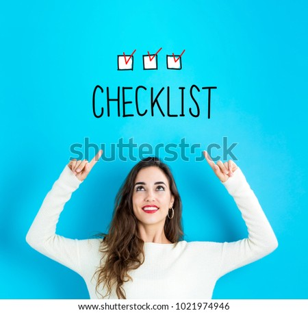 Checklist with young woman reaching and looking upwards #1021974946