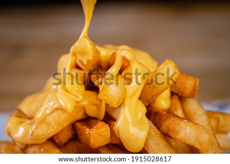 Cheddar Cheese Poured or Pulled from on top Deep Fried French Fries Stock photo ©