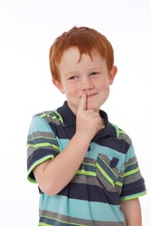 Cheeky red head boy thinking with finger on lips and smiling