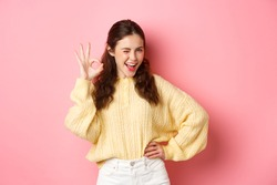 Cheeky young woman winking, showing okay sign, give her approval, like and approve good thing. Girl make OK gesture to give permission, say yes, standing over pink background