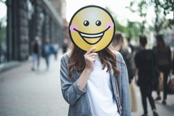 Cheer up. Waist up portrait of lady is standing in the street with yellow laughing emoticon. She is replacing her face with smiley