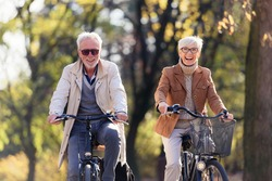 Cheerful active senior couple with bicycle in public park together having fun. Perfect activities for elderly people. Happy mature couple riding bicycles in park