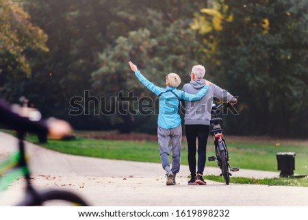Cheerful active senior couple with bicycle walking through park together. Perfect activities for elderly people.