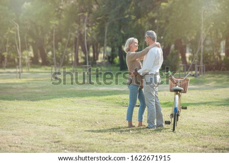 Cheerful active senior couple with bicycle walking through park together. Perfect activities for elderly people in retirement lifestyle.