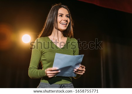 cheerful actress performing role with screenplay on stage in theatre