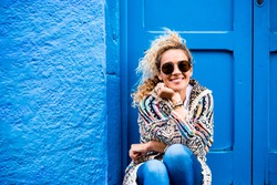 Cheerful adult beautiful woman portrait in the blue color - happy people sit down outside home and enjoy time - pretty young female with blue door and wall in background