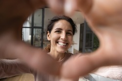 Cheerful affectionate hispanic woman take romantic selfie portrait looking at camera through heart of joined fingers. Enamored young lady shoot love confession to beloved man on video at Valentine day