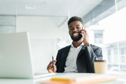 cheerful african american businessman talking on phone in the office