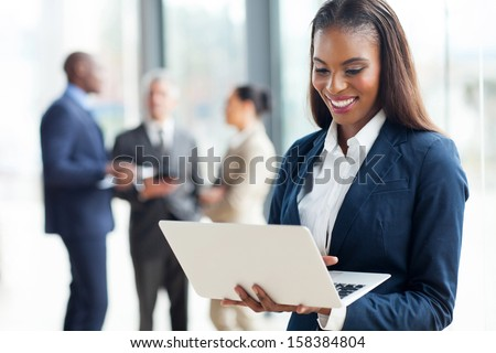 cheerful african american businesswoman using laptop in office