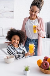cheerful african american child holding orange juice while looking at camera near smiling mother