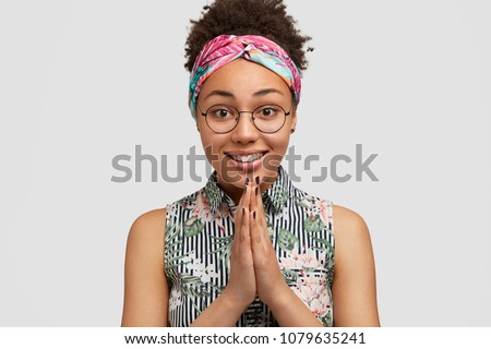 Cheerful African American female model keeps hands together in praying gesture, expresses hope and please, has some request, poses against white background. Dark skinned woman asks for forgiveness #1079635241
