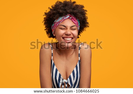 Cheerful African American female with positive expression, giggles joyfully, has broad smile, wears headband and sailor t shirt, being delighted to have many days off, isolated over yellow background