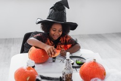 cheerful african american girl in witch halloween costume near pumpkins and cookies on table