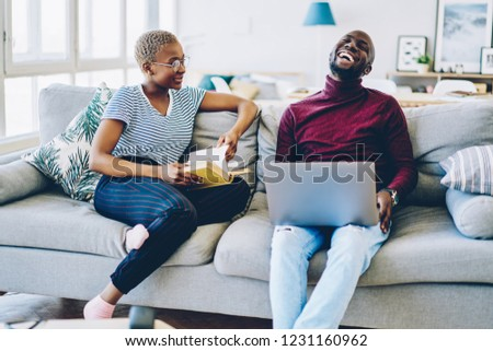 Cheerful african american hipster guy laughing during conversation with girlfriend at home interior, couple sitting at comfortable sofa on leisure man using netbook while his girlfriend read book