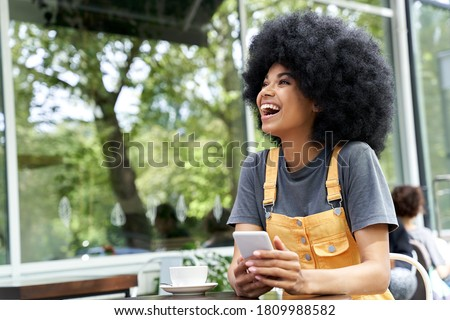 Cheerful African American hipster woman using phone, laughing, sitting at outdoor cafe table. Smiling happy mixed race black lady with afro hair having fun or feeling excited holding smart phone.