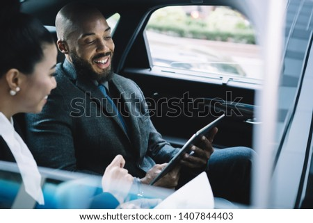 Cheerful African American male director communicating with female secretary during car drive to business meeting discussing startup ideas and reading notes for presentation from digital tablet