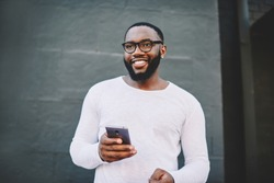Cheerful african american male in spectacles using mobile phone outdoors looking waya and smiling, positive dark skinned hipster guy in white shirt with copy space for brandname holding cellular