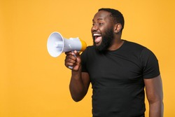 Cheerful african american man in casual black t-shirt isolated on yellow background studio portrait. People sincere emotions lifestyle concept. Mock up copy space. Scream in megaphone, looking aside