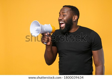 Cheerful african american man in casual black t-shirt isolated on yellow background studio portrait. People sincere emotions lifestyle concept. Mock up copy space. Scream in megaphone, looking aside Stock photo ©