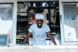 cheerful african american man in chef uniform and hat smiling from food truck