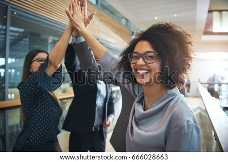 Cheerful African-American office worker giving high five to colleagues and looking at camera.