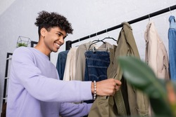 Cheerful african american showroom proprietor looking at clothes on hanging rack