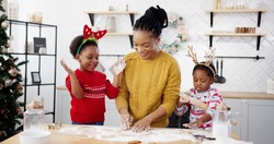 Cheerful African American woman in apron with little kids standing at table in home Christmassy decorated kitchen and having fun while making xmas cookies. Holidays concept