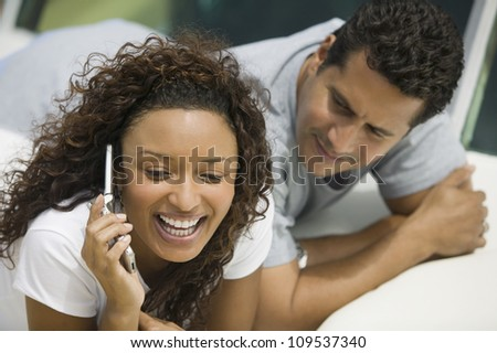 Cheerful African American woman using cell phone with man looking at her