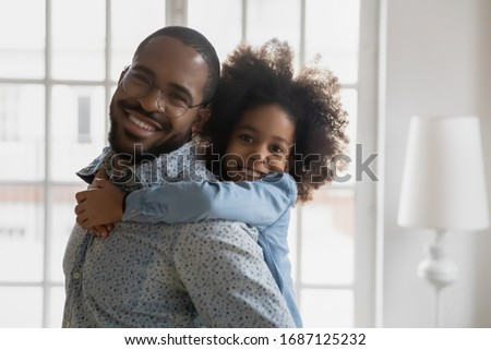 Cheerful african dad play with little child carrying on back daughter having fun together at home. Sweet kid girl piggybacks young handsome father in glasses. Happy american family head shot portrait