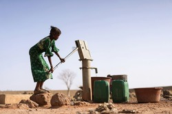 Cheerful African ethnic Girl Bringing Crisp Water in a village