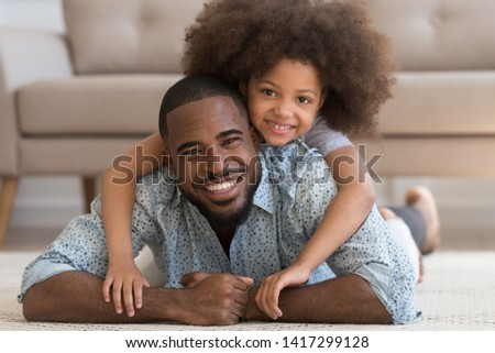 Cheerful african family single black father and cute funny little child daughter portrait, happy dad lying on carpet floor carrying small mixed race kid girl on back smiling looking at camera at home